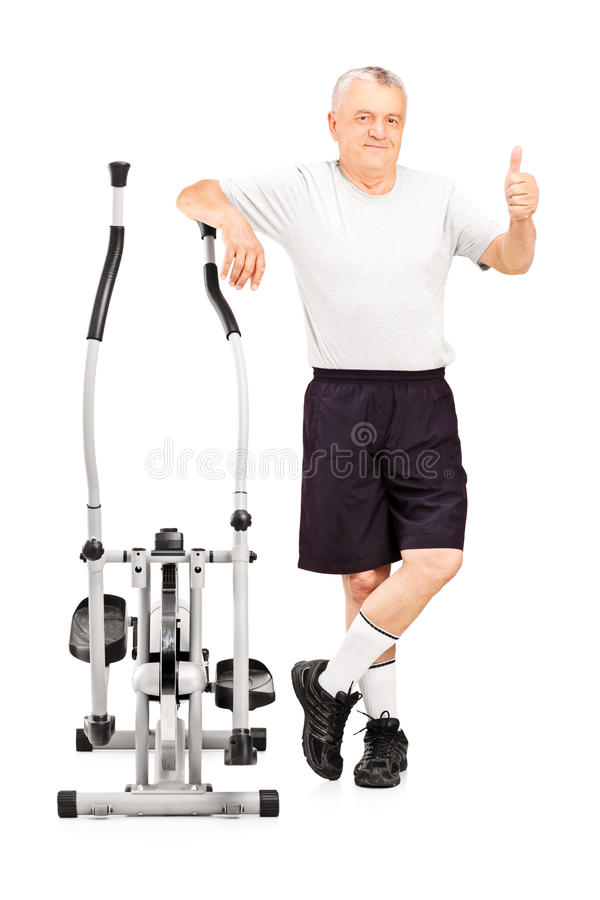 Smiling mature athlete next to a cross trainer giving thumb up