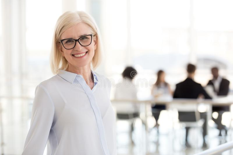 Smiling mature attractive businesswoman in glasses looking in ca. Mera, happy friendly middle aged female executive, older team leader or business coach mentor stock image