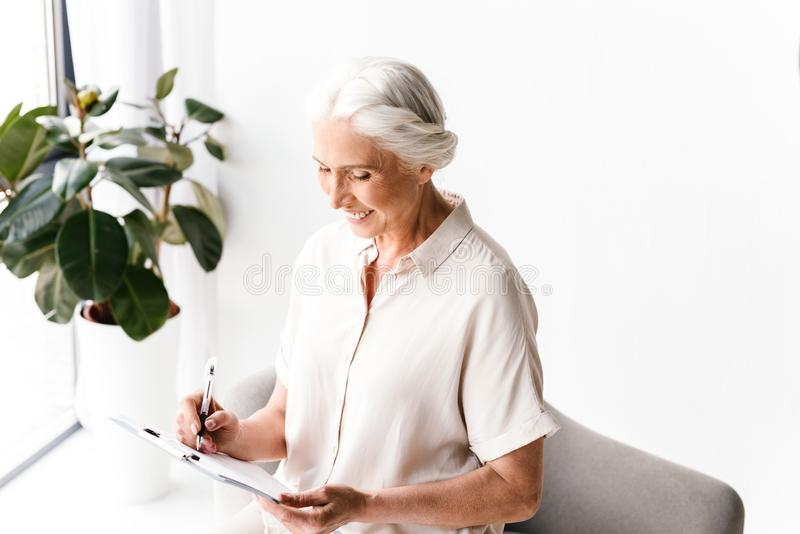Smiling mature business woman taking notes stock photography