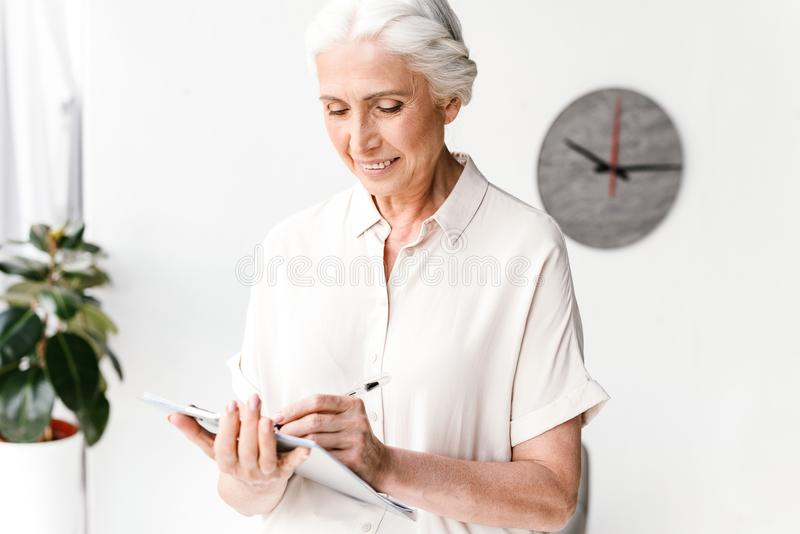 Smiling mature business woman taking notes stock photos