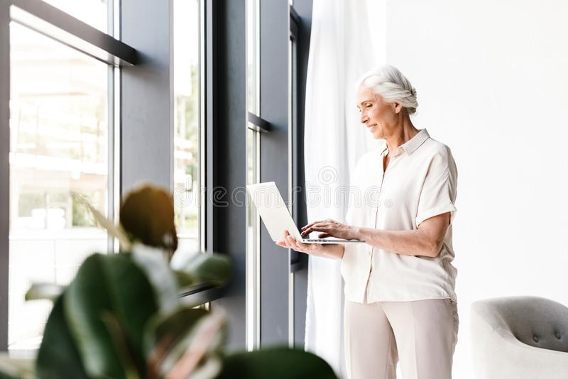 Smiling mature business woman working on laptop royalty free stock images