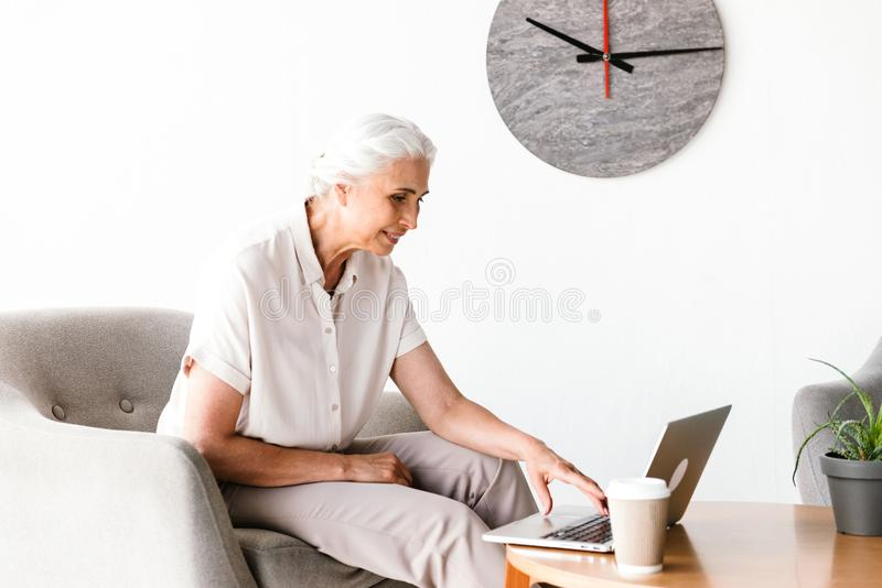 Smiling mature business woman working on laptop royalty free stock photos