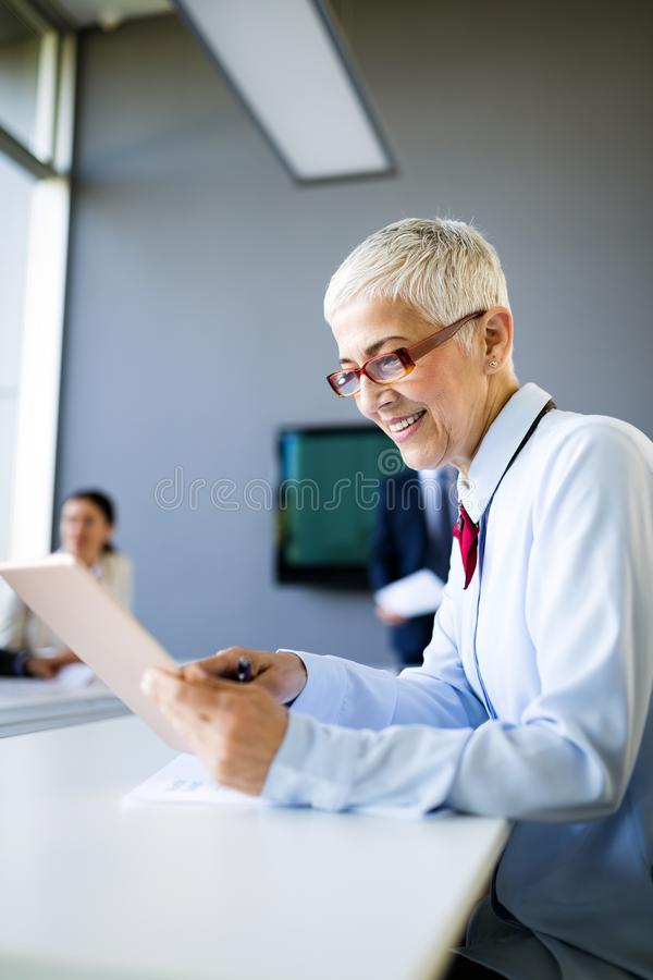 Smiling mature business woman working at modern office stock image