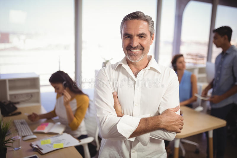 Smiling mature businessman with arms crossed standing in creative office royalty free stock photography