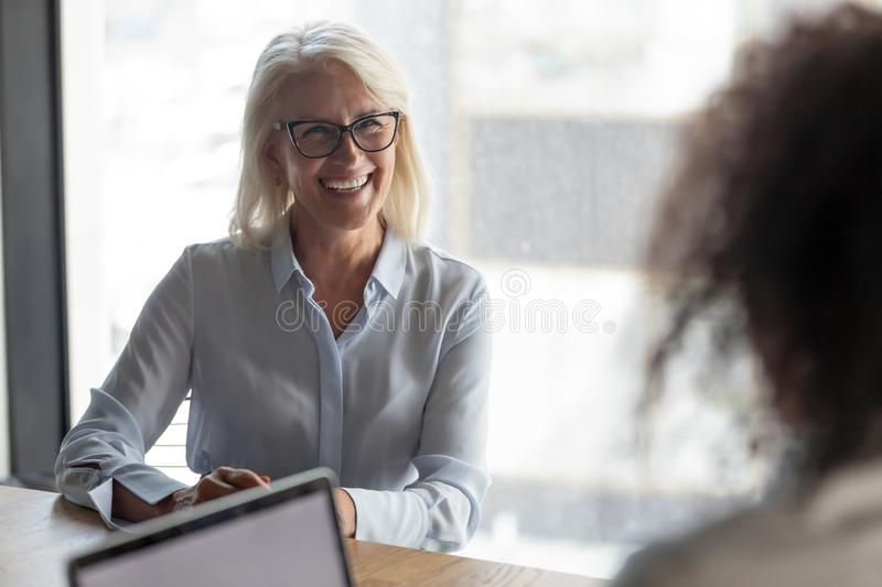 Smiling mature businesswoman candidate answering hr manager questions royalty free stock photos