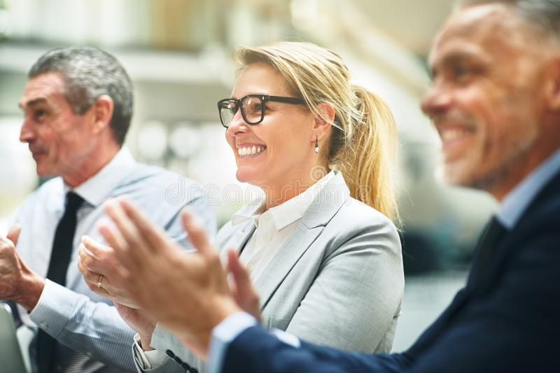 Smiling mature businesswoman and colleagues clapping during an o stock images