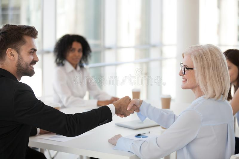 Smiling mature businesswoman and young businessman shaking hands. Greeting introducing at meeting, handshake as concept of good first impression or deal stock photos