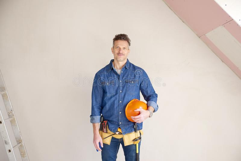 Smiling mature construction man portrait with handyman belt and stock photography