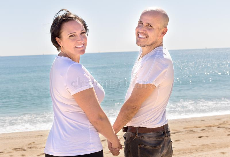 Mature couple on the beach holding hands and looking back royalty free stock images