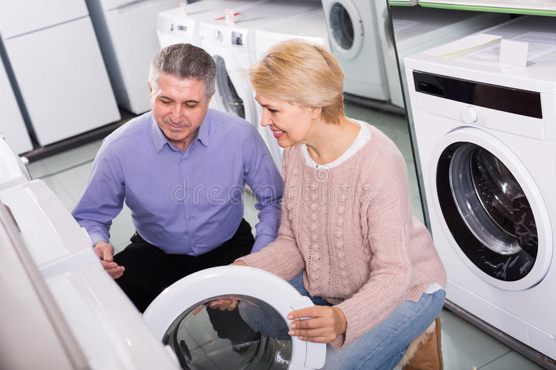 Smiling mature couple chooses washing machine for their house in stock photography
