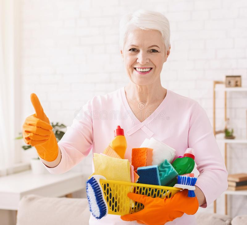 Smiling mature housewife cleaning floor at home royalty free stock photos