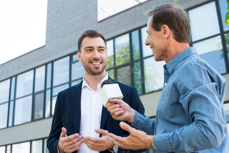 smiling mature journalist takig interview with successful stock photo