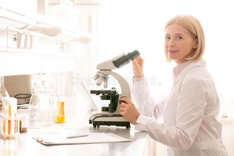 Smiling mature lady in laboratory. Portrait of smiling confident mature lady with blond hair wearing white coat sitting lab bench and using microscope in royalty free stock images