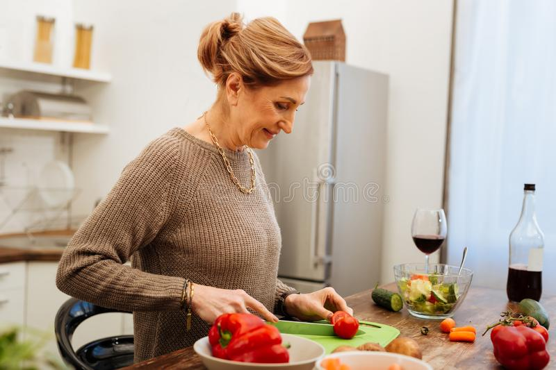 Smiling mature lady with tied hair dealing with long knife royalty free stock photos