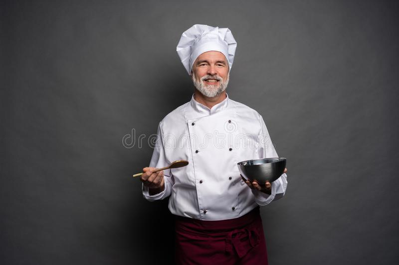 Smiling mature male chef with bowl and cooking vane in hands on black background. royalty free stock images