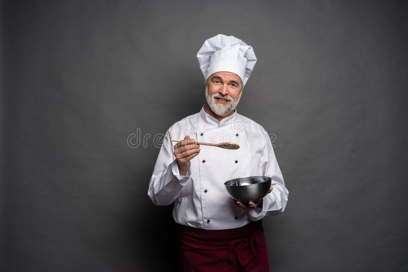 Smiling mature male chef with bowl and cooking vane in hands on black background. royalty free stock image
