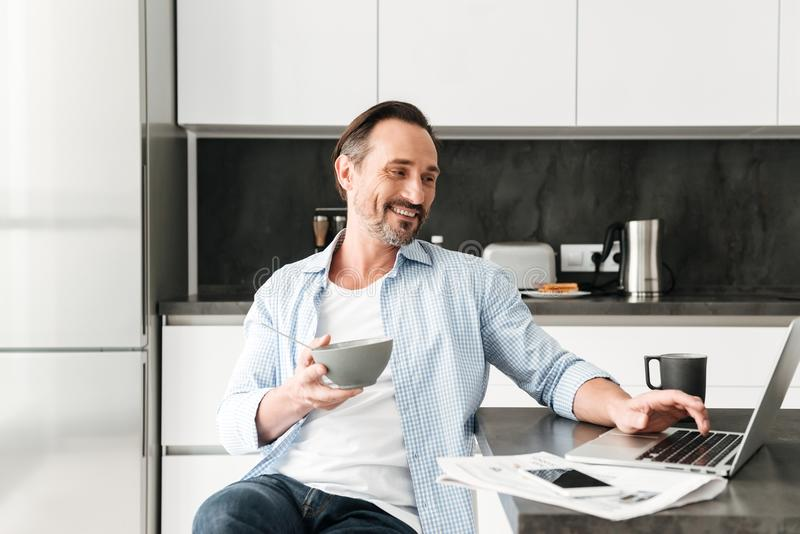 Smiling mature man having healthy breakfast. While sitting at the kitchen table with laptop computer at home stock images