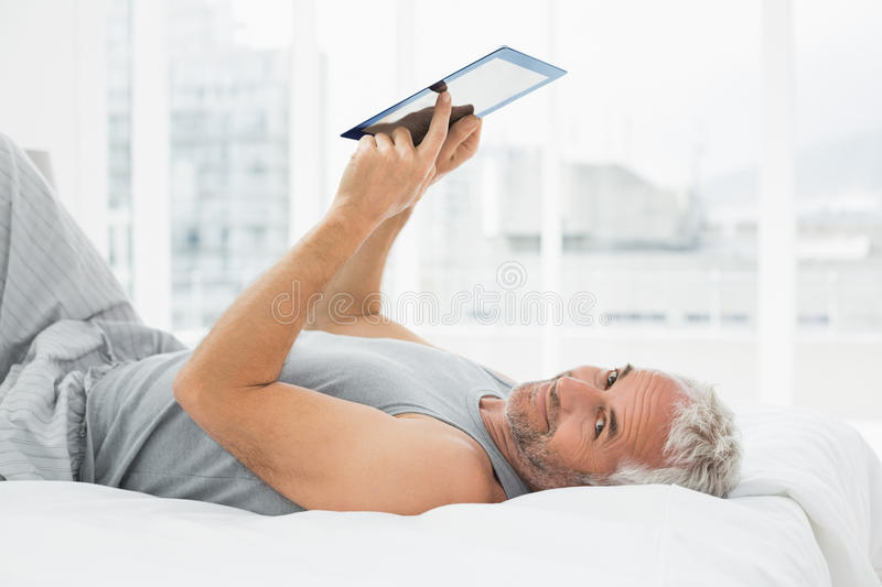 Smiling mature man resting with digital tablet in bed royalty free stock photos