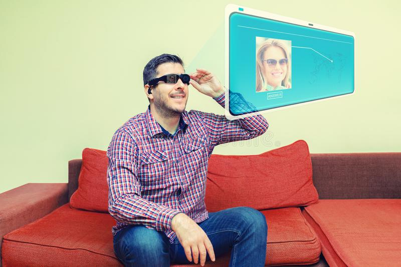 Smiling mature man using modern digital AI goggles for virtual call on hologram screen stock photography