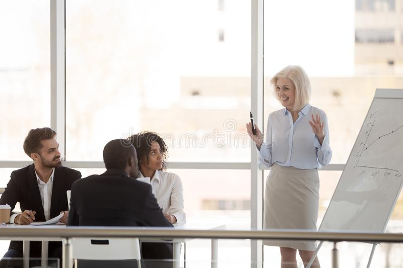 Smiling mature mentor give flipchart presentation to employees stock photo