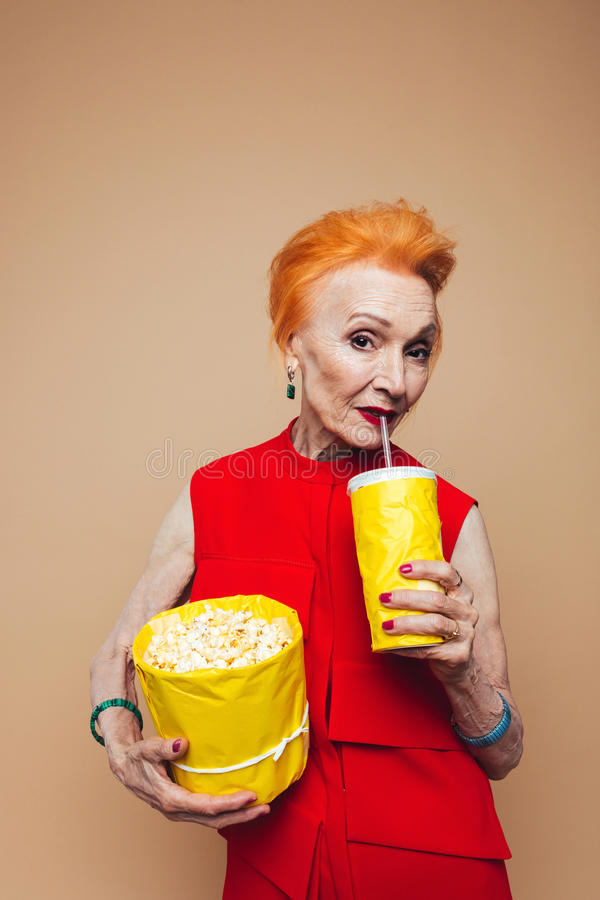 Smiling mature redhead fashion woman eating popcorn. Picture of smiling mature redhead fashion woman standing isolated at studio eating popcorn and drinking stock photos