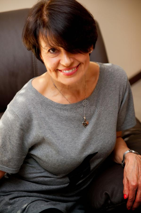 Smiling mature woman on armchair royalty free stock image