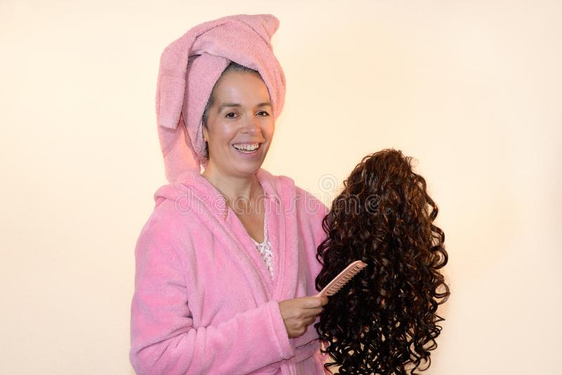 Smiling mature woman combing wig Pink bathrobe. A woman over fifty wearing a pink bathrobe and a towel around her hair, is holding a curly wig and a comb in her royalty free stock photos
