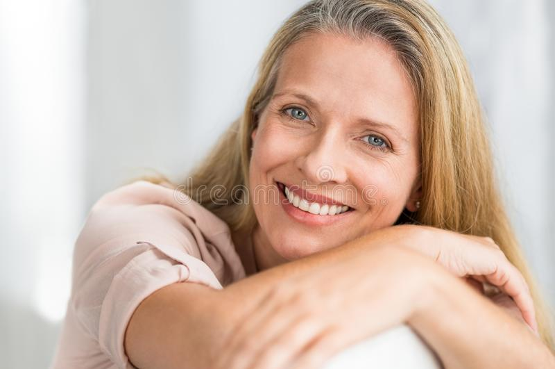Smiling mature woman on couch royalty free stock images