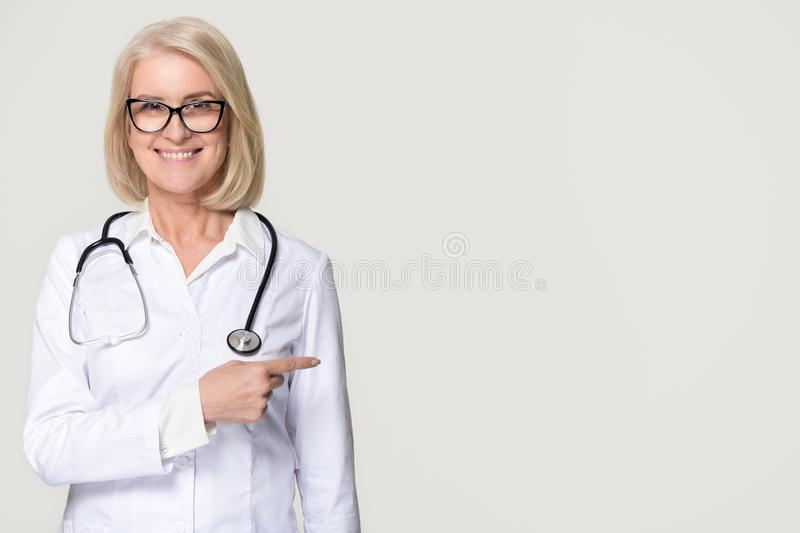 Smiling doctor with stethoscope pointing at copyspace isolated on background royalty free stock images