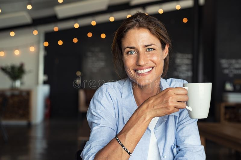 Smiling mature woman drinking coffee stock image