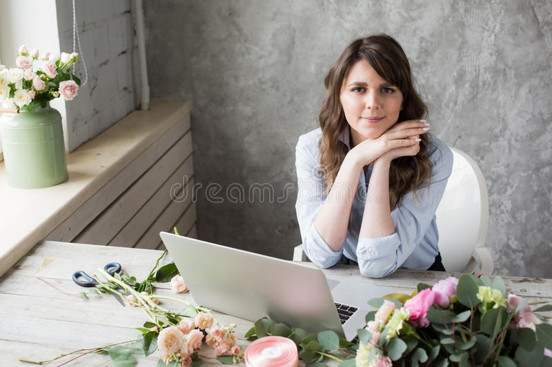 Smiling Mature Woman Florist Small Business Flower Shop Owner. She is using her telephone and laptop to take orders for stock photos