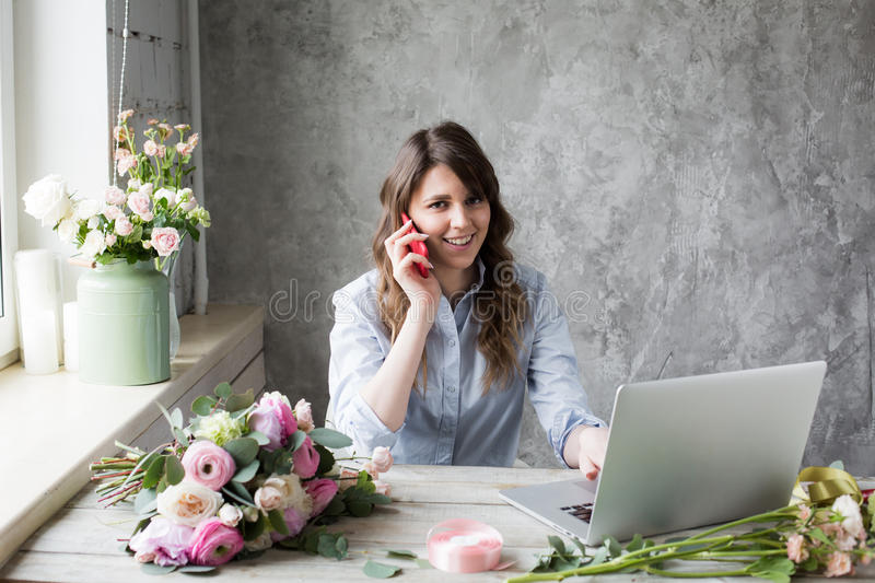 Smiling Mature Woman Florist Small Business Flower Shop Owner. She is using her telephone and laptop to take orders for royalty free stock images