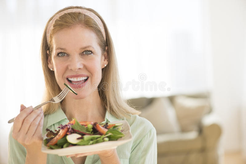 Smiling Mature Woman Having Healthy Salad At Home stock photo