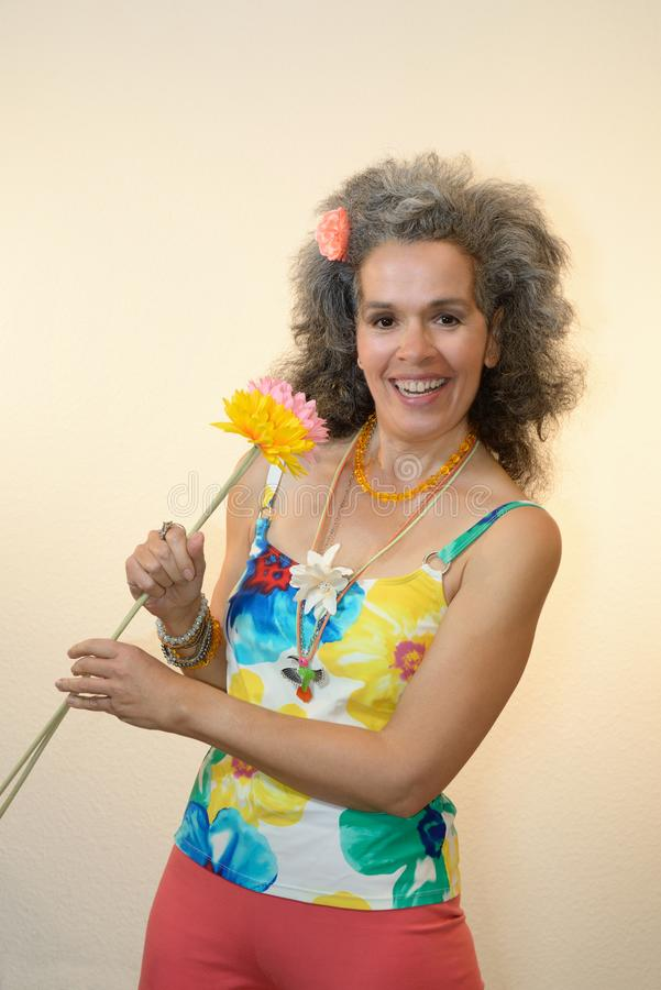 Smiling mature woman holding flowers Summer outfit. A happy slim woman over fifty with graying hair is holding textile flowers and is wearing a colorful floral royalty free stock images