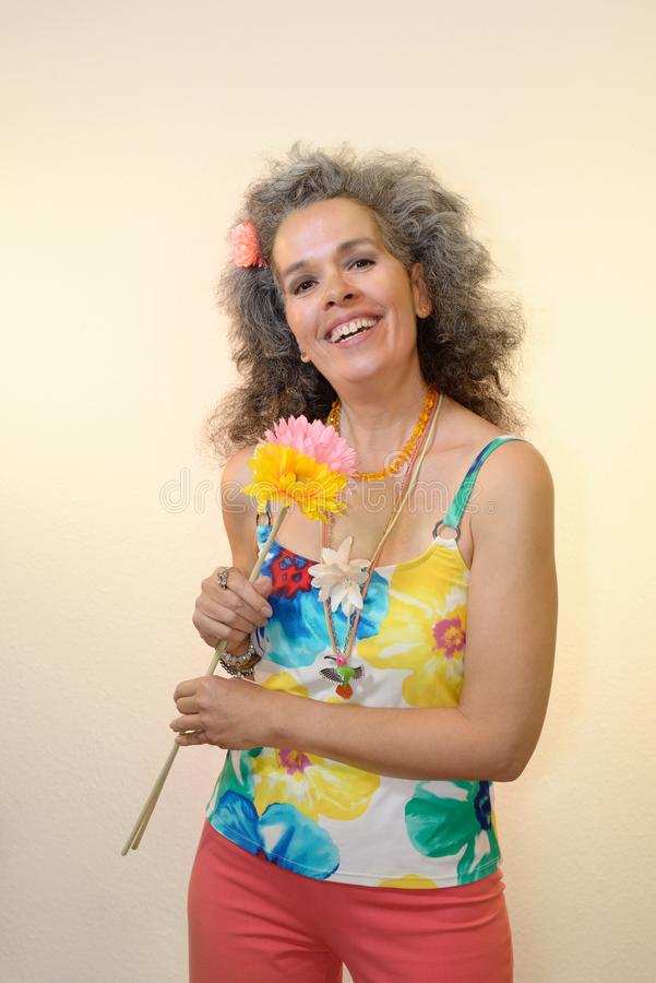 Smiling mature woman holding flowers Summer outfit. A happy slim woman over fifty with graying hair is holding textile flowers and is wearing a colorful floral stock photos
