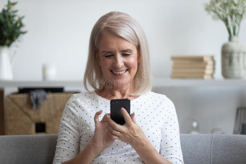 Smiling mature woman holding phone, using mobile device apps royalty free stock image