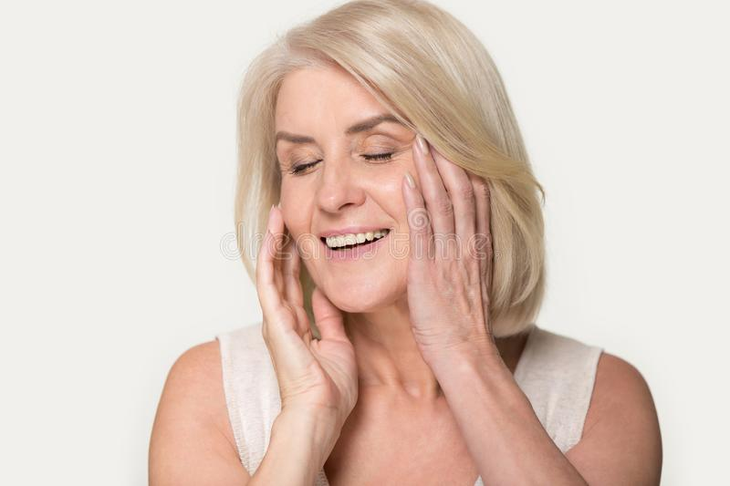 Smiling senior woman touch healthy face skin after beauty procedure royalty free stock images