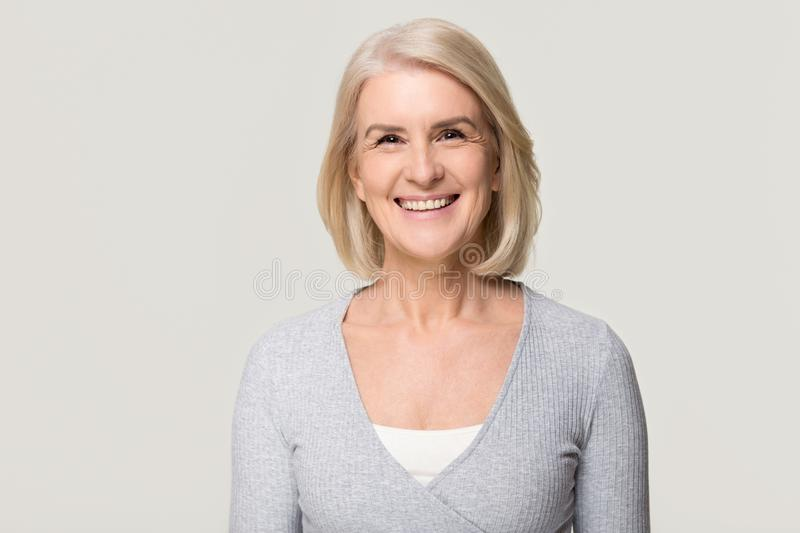 Smiling mature woman looking at camera isolated on grey background royalty free stock photography
