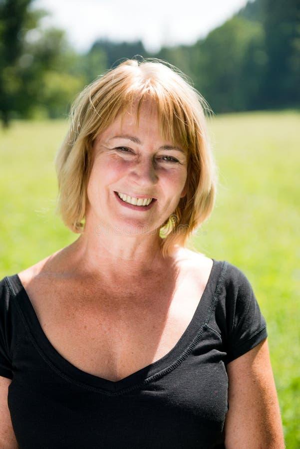 Smiling mature woman outdoor portrait stock photos