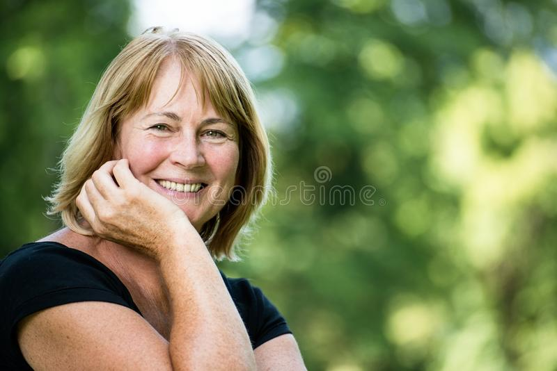 Smiling mature woman outdoor portrait royalty free stock photography