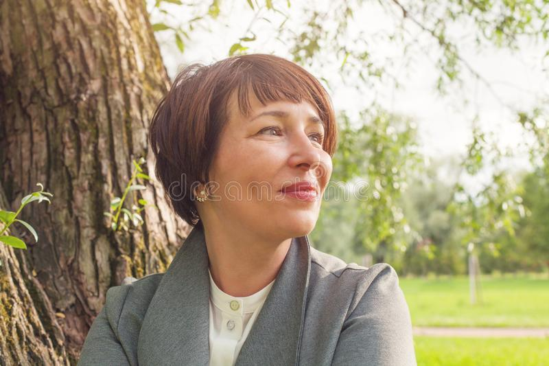 Smiling mature woman resting outdoors, face closeup portrait stock image