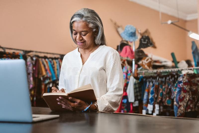 Smiling mature woman writing notes in her fabric shop royalty free stock photos