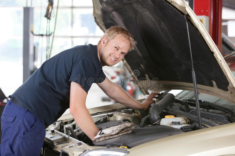 Smiling mechanic working on car. Portrait of a smiling mechanic working on a car in garage stock photography