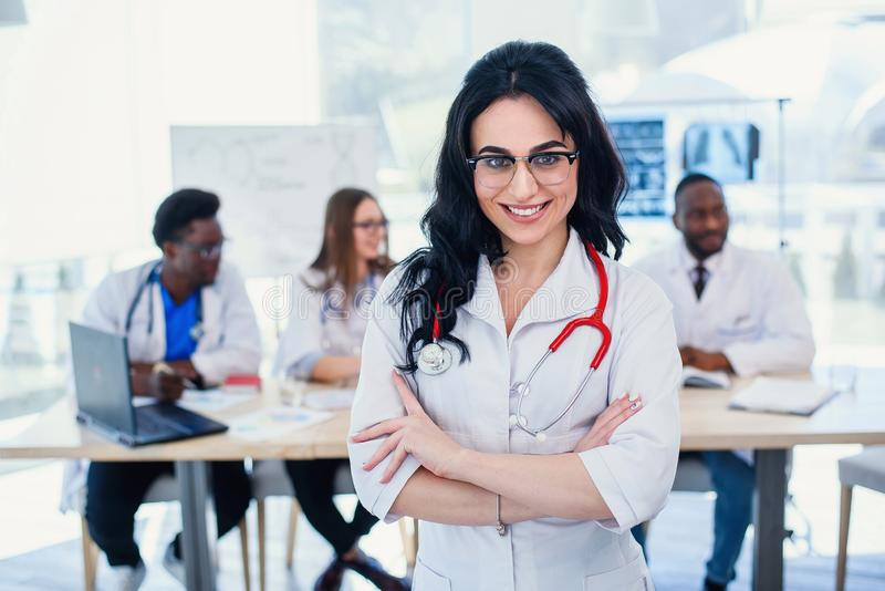 Smiling medical doctor woman with stethoscope standing in front of medic team at hospital. Attractive young female royalty free stock image