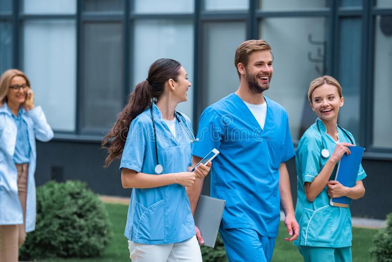 Smiling medical students and lecturer walking on street. Near university stock photo