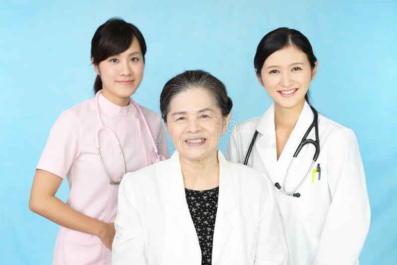 Smiling medical stuff and an old lady stock image