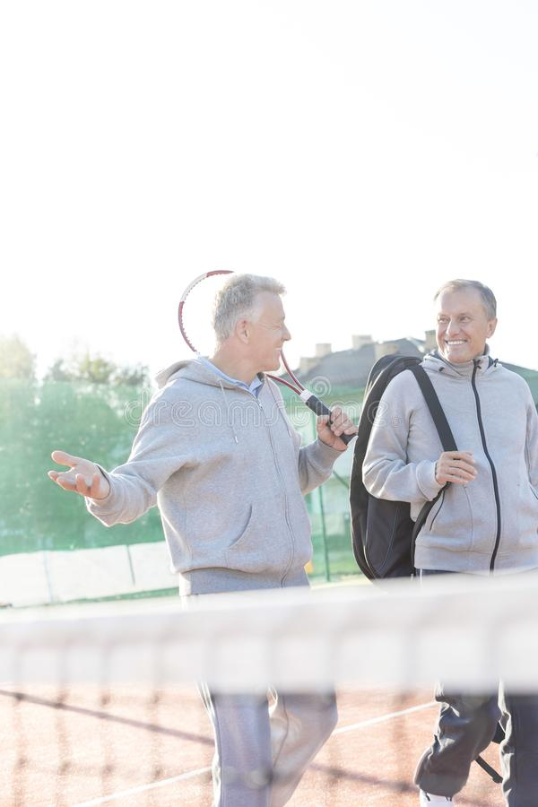 Smiling men in sports clothing talking while walking on tennis court against clear sky royalty free stock photos