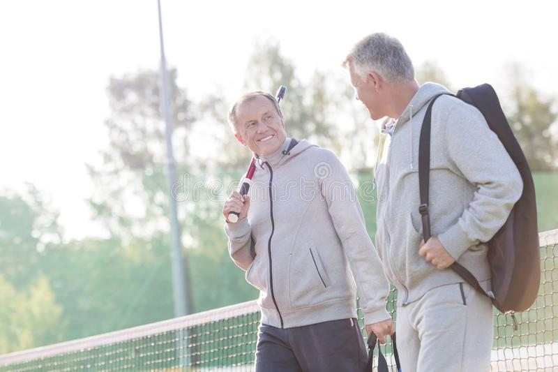 Smiling men in sports clothing talking while walking on tennis court royalty free stock image