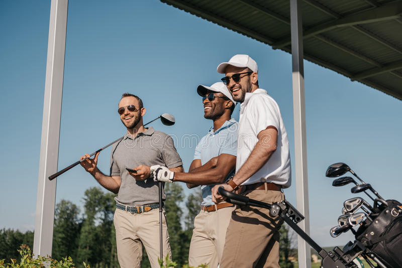 Smiling men in sunglasses holding golf clubs outdoors. Three smiling men in sunglasses holding golf clubs outdoors royalty free stock image
