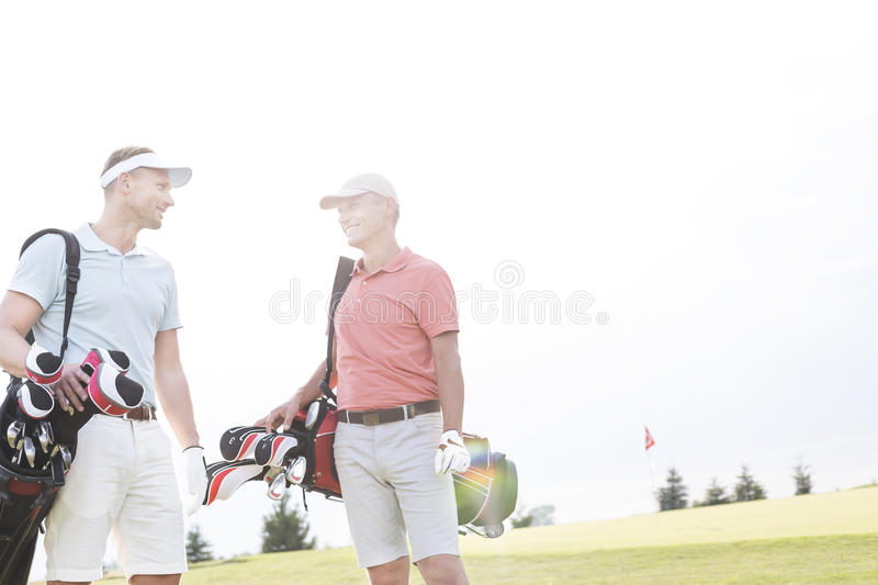 Smiling men talking at golf course against clear sky royalty free stock image